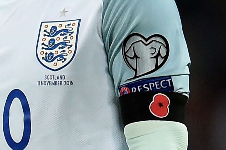 England's captain Wayne Rooney wears a black armband with a poppy during the Fifa World Cup qualifier against Scotland.