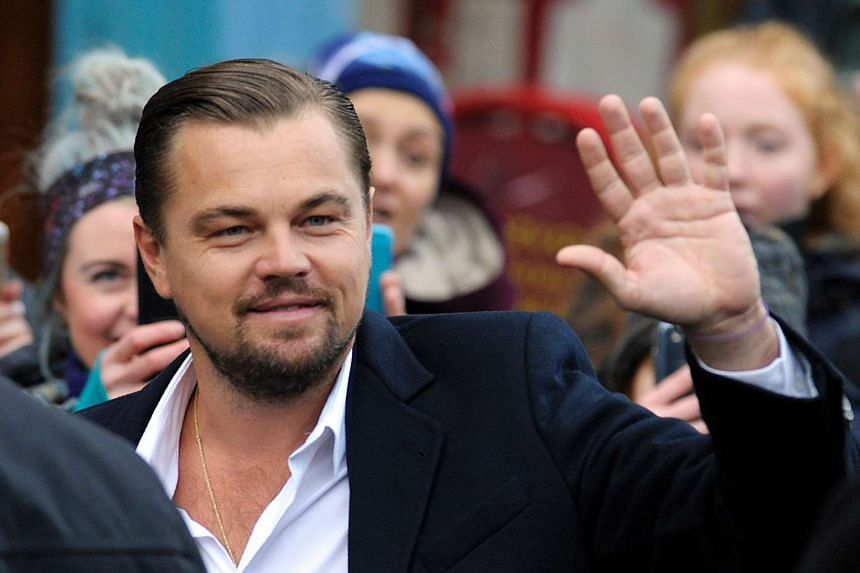 Leonardo Di Caprio waves to fans as he arrives at the social restaurant that aims to help the homeless in Edinburgh.