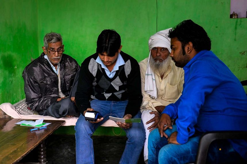 Bank correspondent Mohammad Imran (second from left) inputs bank details of villagers on a mobile banking machine in Basendua village in Bulandshahr, in northern Uttar Pradesh state.
