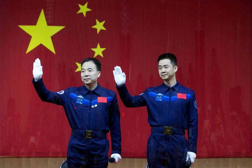Chinese astronauts Jing Haipeng (left) and Chen Dong wave at a news conference before China launches the Shenzhou 11 manned spacecraft, in Jiuquan, China, on Oct 16, 2016.
