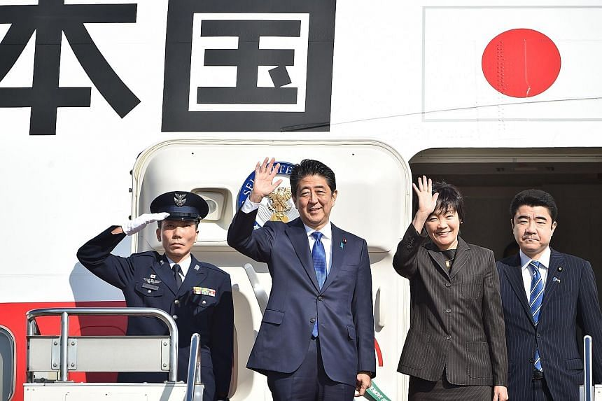 Mr Abe and his wife Akie waving to well-wishers before boarding a government plane at Tokyo's Haneda Airport yesterday. He was due to meet Mr Trump late yesterday at Trump Tower in New York. Mr Abe is the first foreign leader to meet the US President