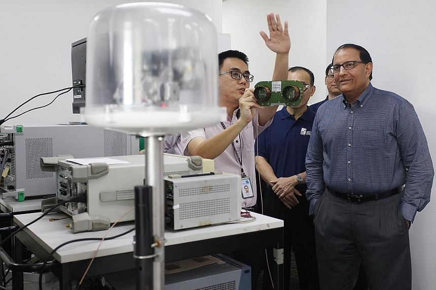 Mr Iswaran observing how a tracking antenna, commonly used in vehicular deployment, responds to a simulated beacon signal in a demonstration by Addvalue Technologies engineer Choong Yoon Hui.