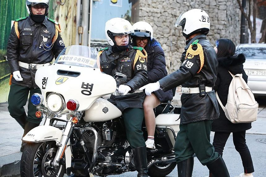 Policemen in Seoul giving a lift to a student taking a crucial college entrance examination yesterday. About 606,000 students in South Korea took the high-stakes annual examination that could earn them a place in one of the elite colleges seen as key