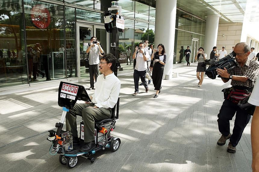 Dr Ang demonstrating how the self-driving mobility scooter works at NUS' University Town yesterday. The Singapore-MIT Alliance for Research and Technology harnessed previously developed software for driverless cars and buggies for use in the scooter,