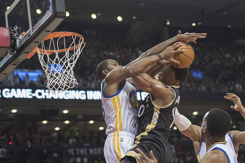 Toronto Raptors guard DeMar DeRozan (middle) drives to the basket as Golden State Warriors forward Kevin Durant (left) attempts to block his shot during the third quarter on Wednesday. The Warriors won 127-121 as Durant and Stephen Curry combined for