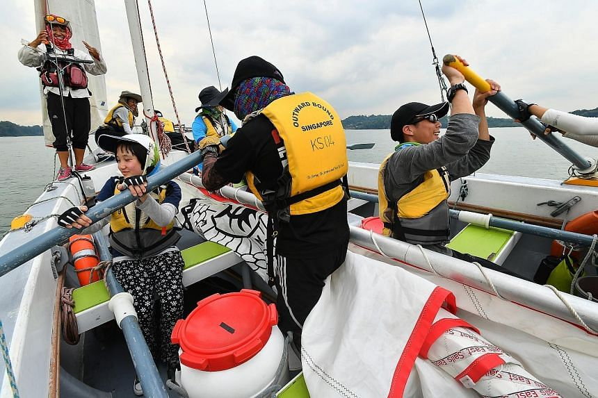 Lee Yan Ling (sitting, left), 14, a student from Rainbow Centre Margaret Drive School, and Loo Yang Rui Erik Lars (sitting, right), 17, a JC 1 student from Serangoon Junior College, rowing in the cutter sailboat on Wednesday as part of Outward Bound