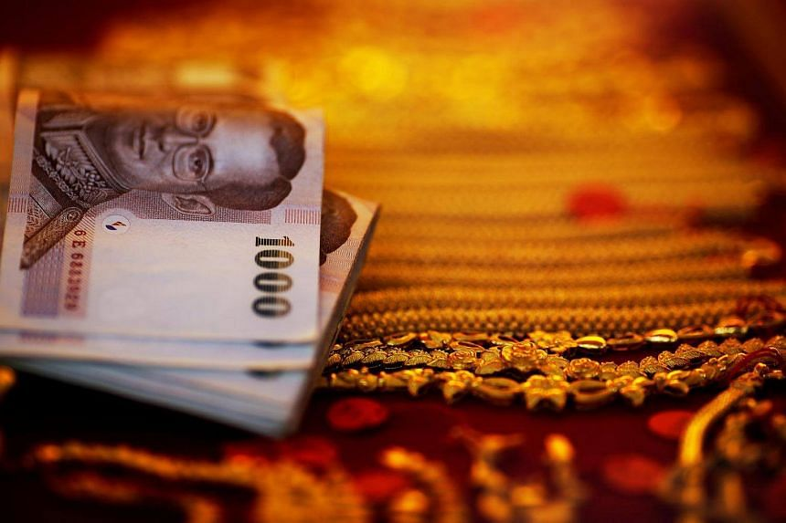 Thai baht banknotes are seen next to gold offered for sale in a gold shop in Bangkok.