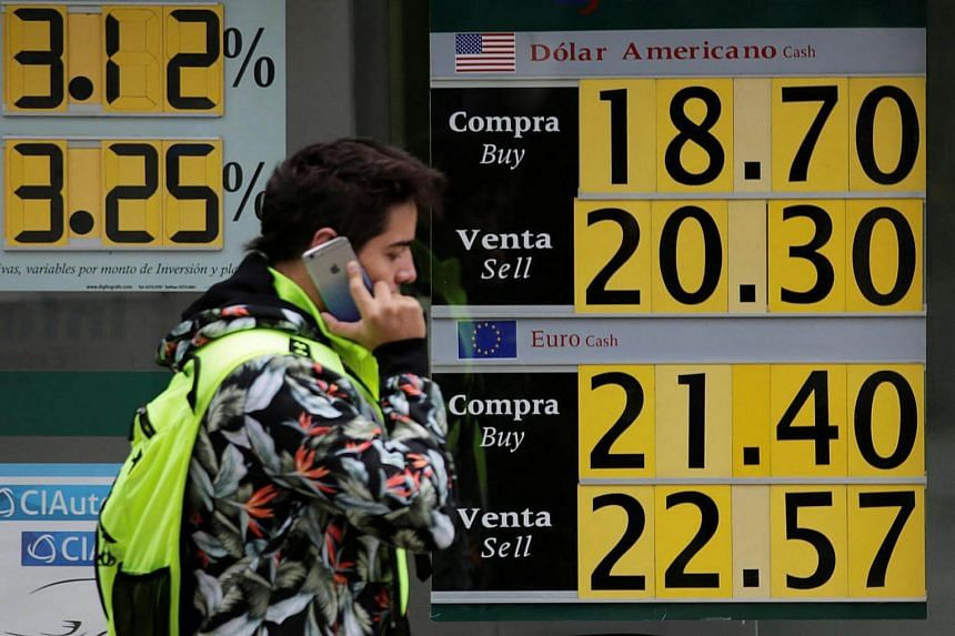 A man walks past a board displaying the exchange rate for Mexican peso against the US dollar and the Euro at a bank in Mexico City on Nov 17, 2016.
