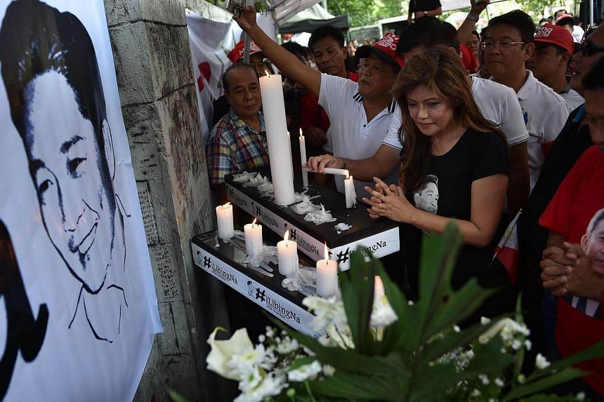 Imee Marcos (centre), daughter of the late dictator Ferdinand Marcos and governor of the family's northern stronghold of Ilocos Norte, offers prayers alongside supporters in front of a portrait of her father at the start of a vigil in front of the Su