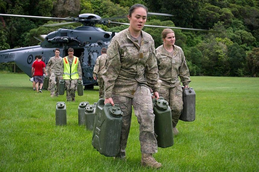Defence personnel unloading water containers from a helicopter as hundreds of tourists are evacuated from Kaikoura.