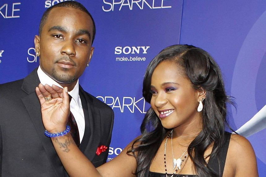 """Bobbi Kristina Brown, daughter of the late singer Whitney Houston, reveals a tattoo with the initials """"W H"""" as she waves while arriving with boyfriend Nick Gordon at the premiere of the new film Sparkle."""