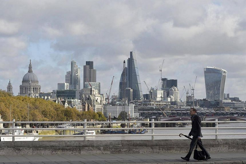 A man crosses Waterloo Bridge with the backdrop of the City of London and the financial district in London, Britain.