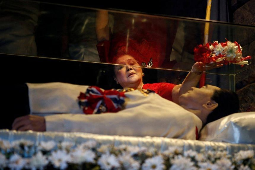 Former first lady Imelda Marcos offering flowers on the glass coffin of her husband, late president Ferdinand Marcos, who remains unburied since his death in 1989, on July 2, 2014.