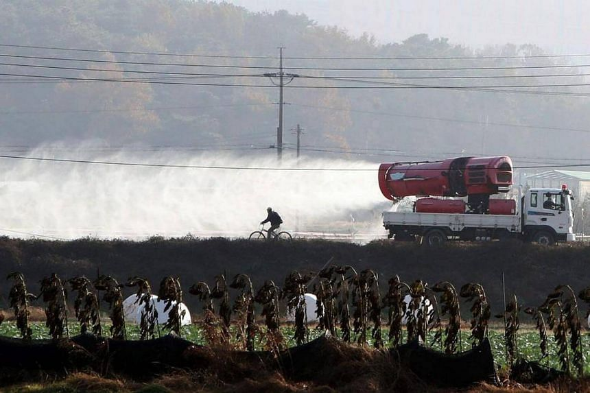 A quarantine vehicle sprays disinfectant along the bank of a stream in Cheonan, Seoul, following the discovery of the avian influenza virus in wild bird excrement.