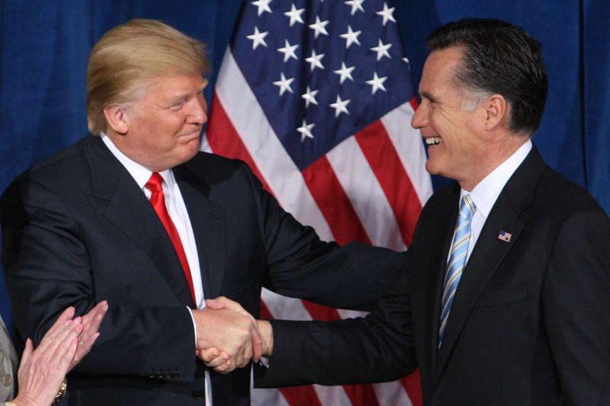 Donald Trump (left) greets Mitt Romney at the Trump Hotel in Las Vegas.