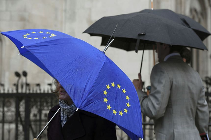 A demonstrator sheltering under an EU umbrella in London last month during a legal challenge to force the British government to seek parliamentary approval before starting the formal Brexit process. The writer says there are three potential doom spirals b