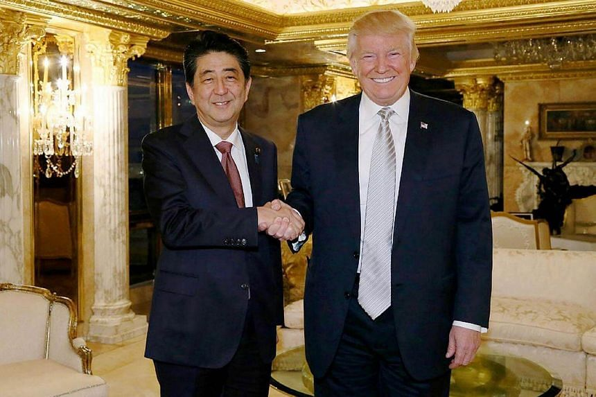 This handout picture from Japan's Cabinet Secretariat released on Nov 18, 2016, shows Japan's Prime Minister Shinzo Abe (left) shaking hands with US President-elect Donald Trump in New York.