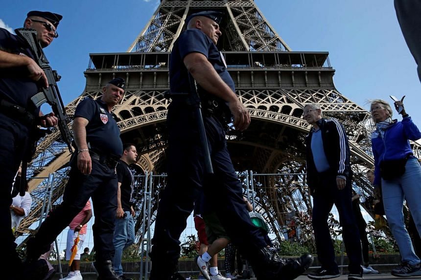 French police patrol as tourists walk by the Eiffel Tower in Paris, Aug 20, 2016.