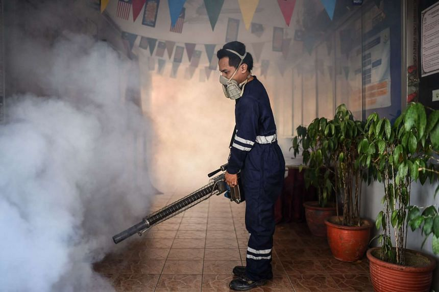 A pest control worker fumigates a school corridor on the eve of the annual national Primary School Evaluation Test in Kuala Lumpur on Sept 4, 2016.