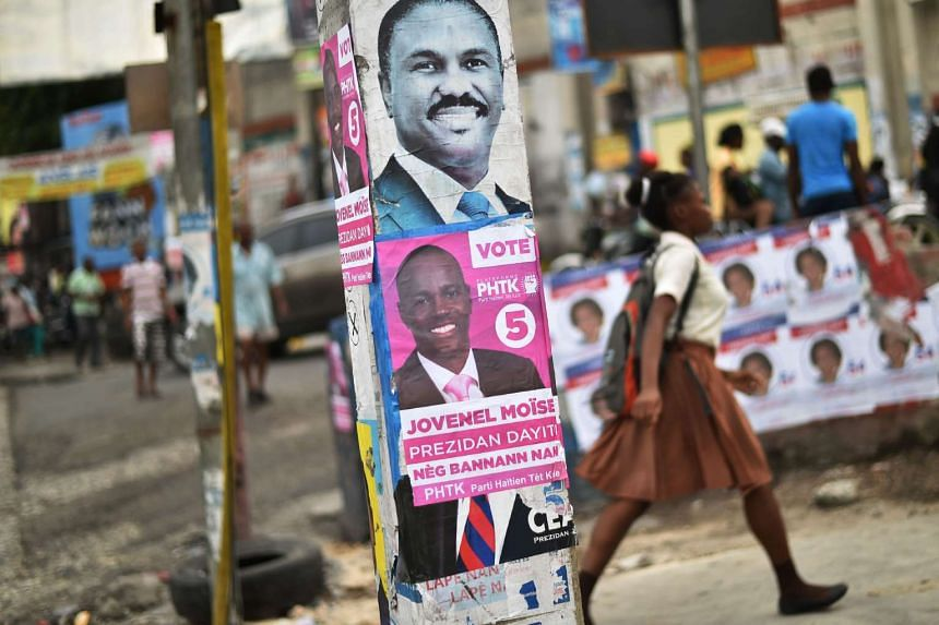 Electoral posters of presidential candidates Jude Celestin (top) of the Lapeh political party and Jovenel Moise (bottom) of the PHTK political party are seen on a street in the commune of Petion Ville in the Haitian capital Port-au-Prince on Nov 15,