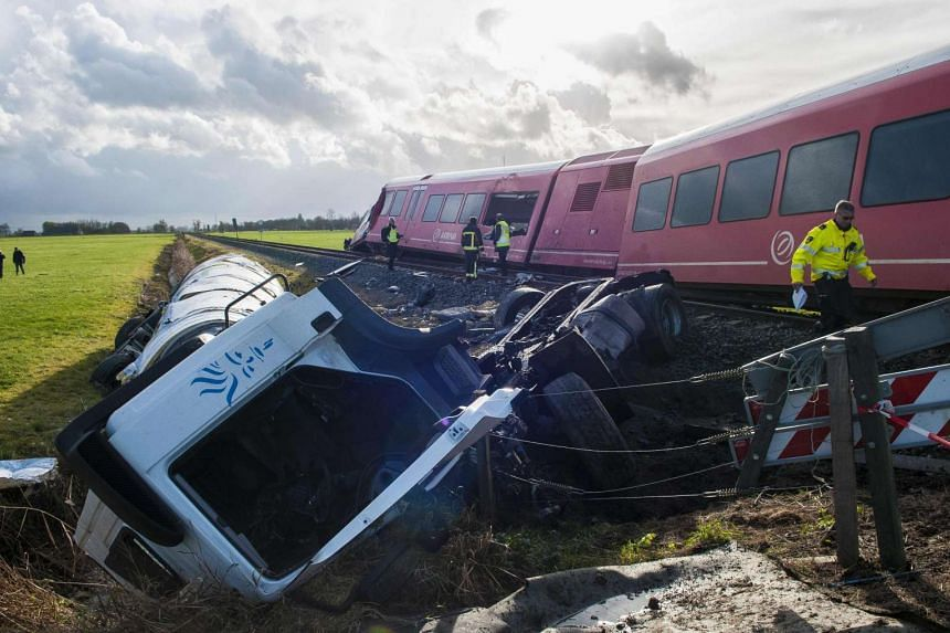 A policeman walks near a derailed passenger train and a smashed milk tanker after a crash near Winsum, on Nov 18, 2016.