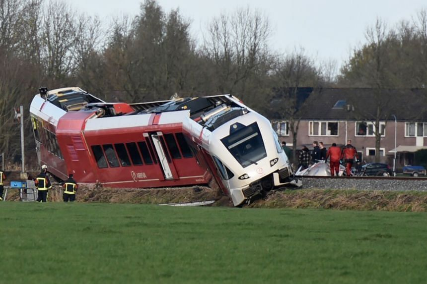 Rescuers work near a derailed passenger train after a crash with a milk tanker near Winsum, on Nov 18, 2016.