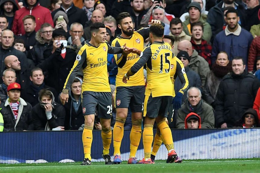 Arsenal's French striker Olivier Giroud (second left) celebrates scoring with teammates.