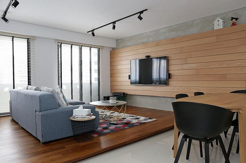 The living room (above) has a feature wall that comprises oak panelling against a cement screed wall. The master bedroom (left) features a walk-in wardrobe behind the bed. Mr Jake Chia and Ms Astee Lim (right) created a nursery (left) with glass pane