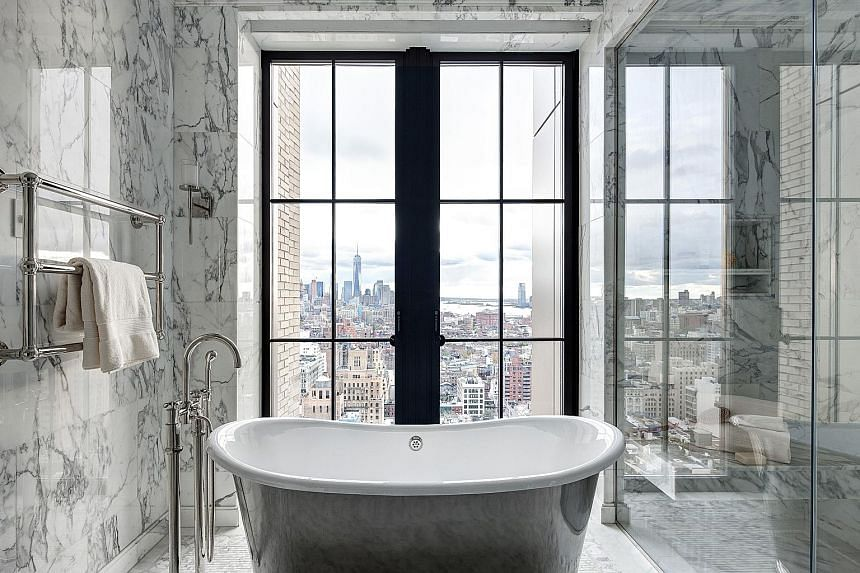 Designed by Uruguayan architect Rafael Vinoly, the 432 Park Avenue residential skyscraper has bathrooms with panoramic views from the tub (left). Large windows and less privacy are among the trends in bathroom design, as seen in this one (above) in W