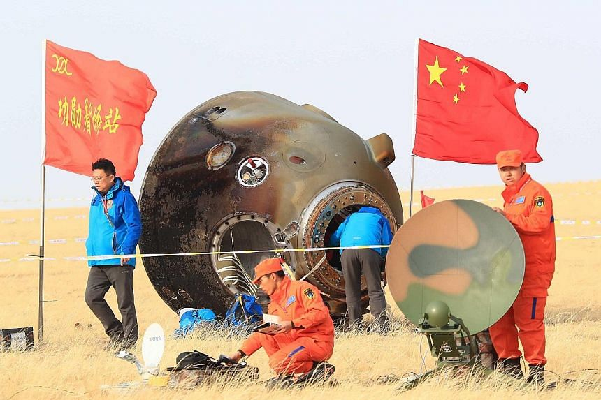 The Shenzhou 11 space capsule after its successful landing in Inner Mongolia yesterday. Ground personnel planted two flags beside the capsule after it touched down.