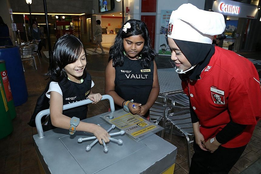 Elie Nur Aisha Johari (left) and Arun Thirral Amiltham Alarmugill at the KidZania Singapore party. Kids also learnt about managing money at the Maybank-sponsored event.
