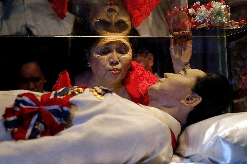 Former first lady Imelda Marcos kissing the glass coffin of her husband Ferdinand Marcos during her 85th birthday celebrations in July 2014 in his hometown of Batac, Ilocos Norte province, in the northern Philippines.