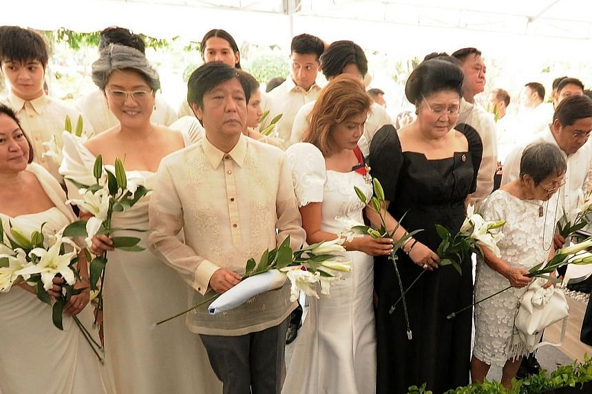 Left: Mrs Marcos (in black) attending Mr Marcos' burial at the National Heroes' Cemetery in Manila yesterday. With her are their son Ferdinand Marcos Jr and daughters Imee (fourth from right) and Irene (second from left). The burial came less than 10