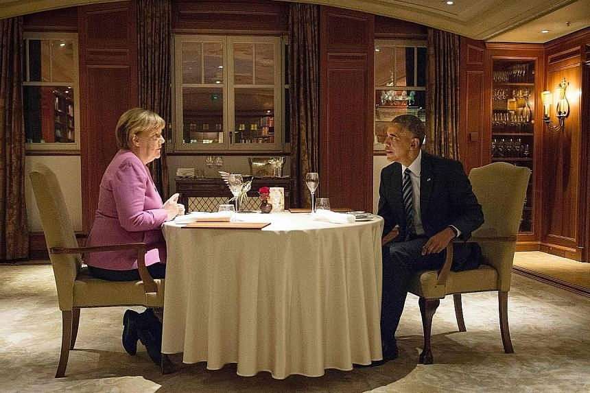 Dr Merkel and Mr Obama having dinner at the Hotel Adlon in Berlin on Wednesday. Giving a ringing endorsement for the German Chancellor before she announces whether she will run for a fourth term in next year's elections, Mr Obama acknowledged the bur