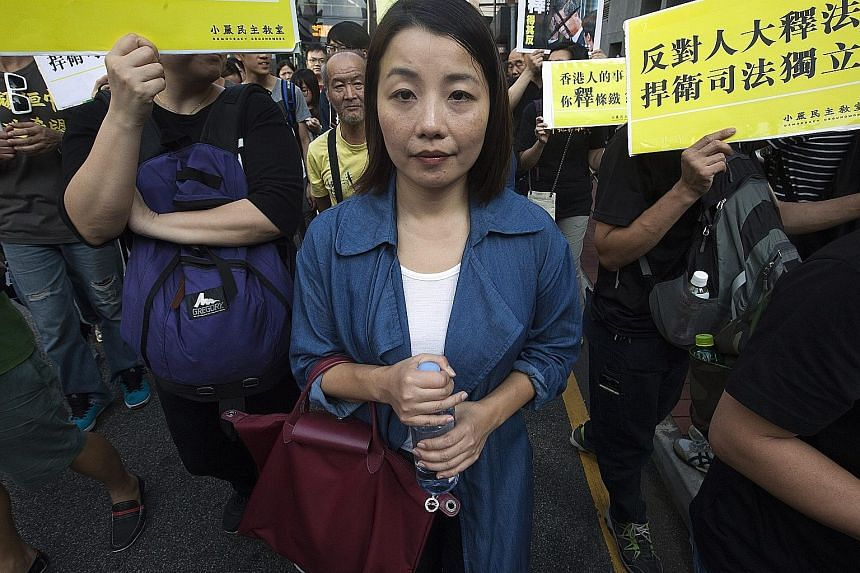 Ms Lau at a march this month to protest against Beijing's interpretation of Hong Kong's Basic Law over oath-taking in the legislature. The bid to unseat her failed because of delays in the application.