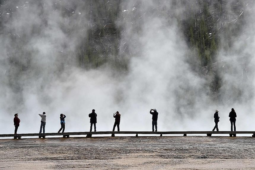 Tourists at the Grand Prismatic Spring in Yellowstone National Park. Visitors have been warned not to stray beyond the park's official paths as much of its wilderness remains untouched.