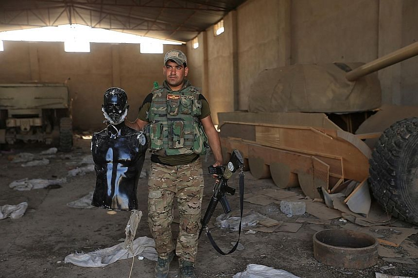 A soldier north of the Iraqi city of Mosul holds a mannequin as he stands beside a wooden tank that was used by militants from the Islamic State in Iraq and Syria to confuse air forces.