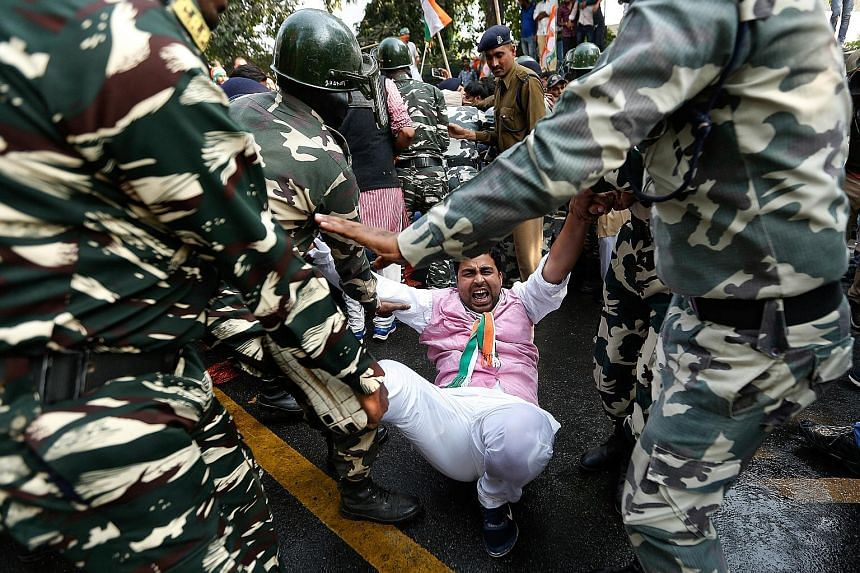 An activist from the youth wing of the opposition Congress party being detained by police during a protest against the government's decision to withdraw 500 and 1,000 rupee banknotes from circulation.