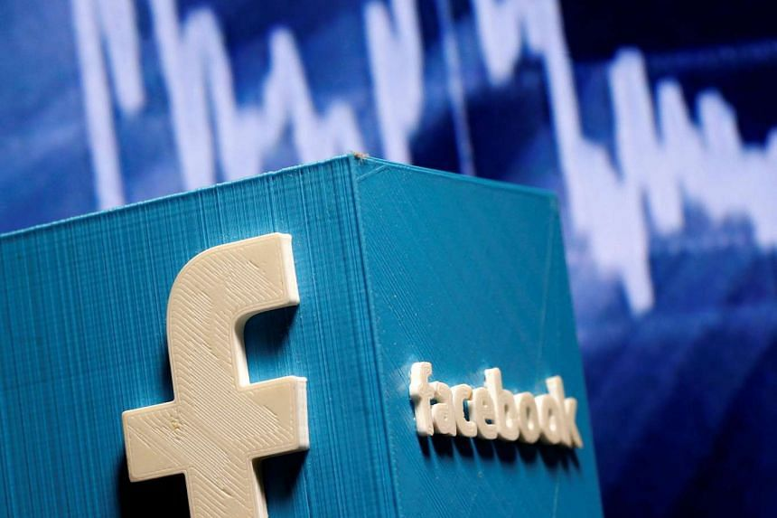 A 3D-printed Facebook logo is seen in front of a displayed stock graph in this illustration.