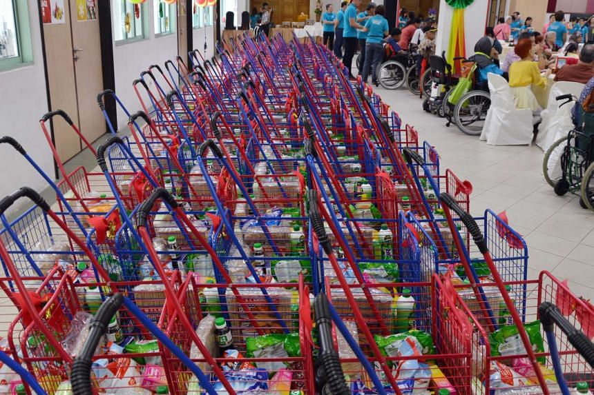 Some 200 needy residents in Marsiling received a free lunch, supermarket vouchers and a trolley full of necessities on Saturday (Nov 19).