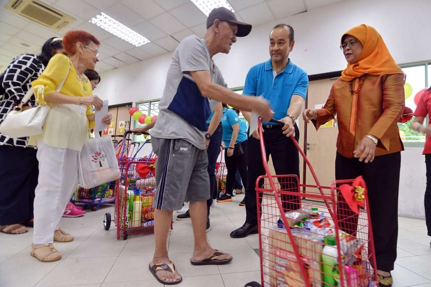 Speaker of Parliament and Marsiling-Yew Tee GRC MP Halimah Yacob presenting a trolley full of necessities on Saturday (Nov 19) to a Marsiling resident.