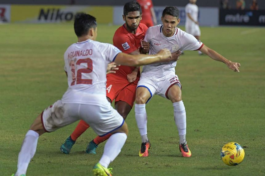 Singapore's Hariss Harun watched by Amani Aguinaldo (left) and Kenshiro Daniels during the Suzuki Cup 2016 match between Singapore and Philippines (white) at the Philippines Sports Stadium, Nov 19, 2016.