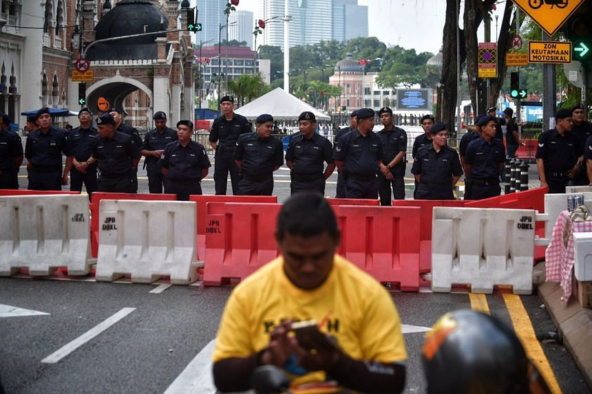 Police guard a barricade placed in front of Merdeka Square.