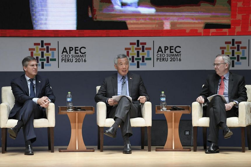 PM Lee Hsien Loong speaking at the CEO Summit. With him are fellow panel speakers Robert E. Moritz, chairman of PwC Global (left), and Stephen McIntosh, group executive growth and innovation at Rio Tinto.
