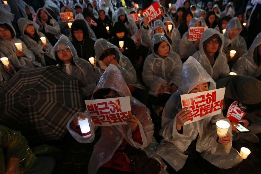 South Korean people attend as they carry placards reading 'Park Geun Hye Out', during a rally against South Korean President Park Geun Hye on a main street in Seoul.