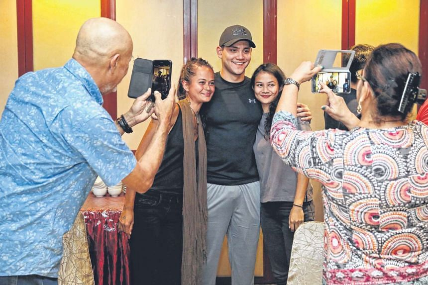 Schooling posing for photos with members of his extended family at Roland Restaurant last night. The 21-year-old swimmer arrived in Singapore to a low-key welcome and spent the day with his loved ones before starting on a series of public appearances