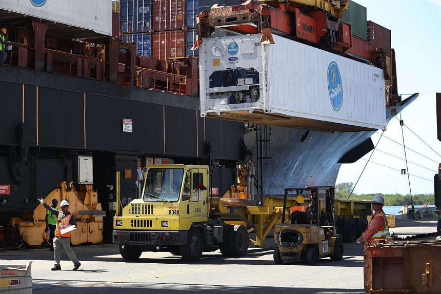 Shipping containers being offloaded from a cargo ship at Port Everglades in Fort Lauderdale, Florida.