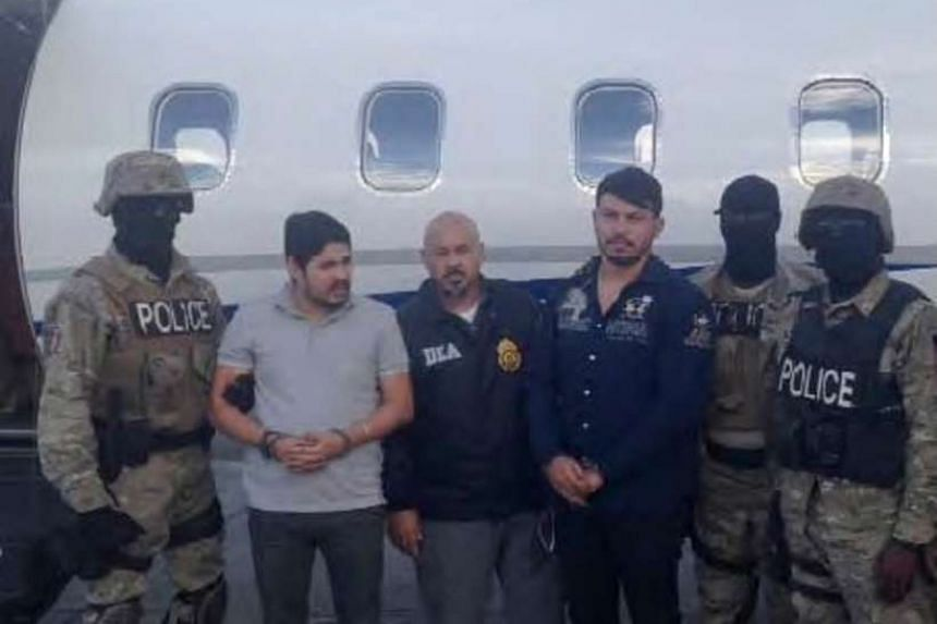 Efrain Antonio Campo Flores (second from left) and Franqui Francisco Flores de Freitas standing with law enforcement officers in this Nov 12, 2015, photo after their arrest in Port Au Prince, Haiti.