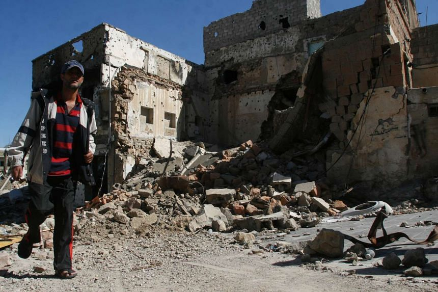 A man walks past a house destroyed during battles between Houthi fighters and pro-government fighters in the south-western city of Taiz, Yemen, on Nov 17, 2016.