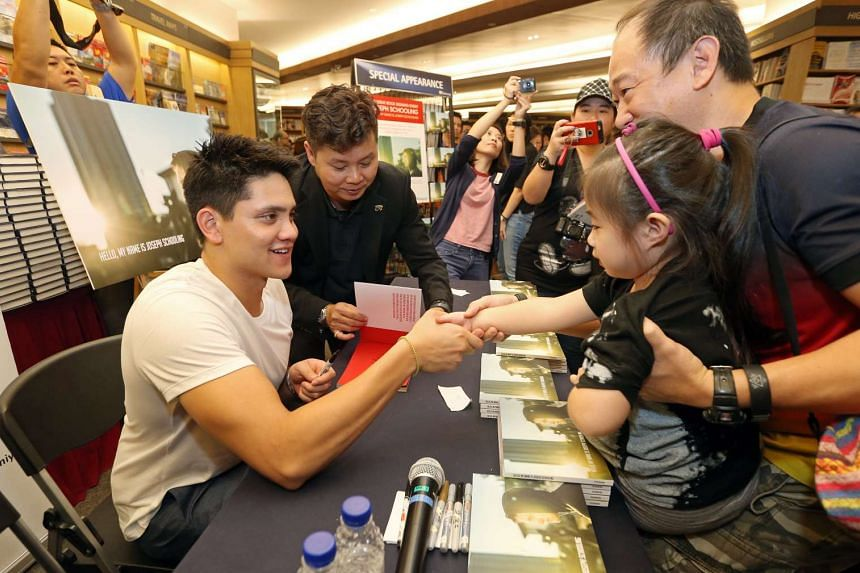 Joseph Schooling greets fan (right) Skylar Chan, 5, and her father Jimmy Chan, 45, at a book signing session at Kinokuniya, Ngee Ann City on Nov 20, 2016.